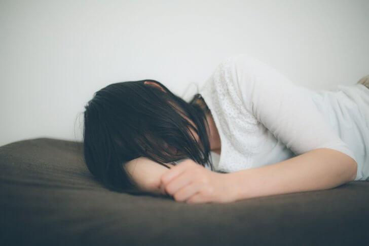ひとり腕枕で寂しさを紛らわす失恋女子 [モデル:たけべともこ]