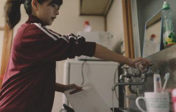溜まった洗い物をする貧乏学生(アパート暮らし) [モデル:千歳]