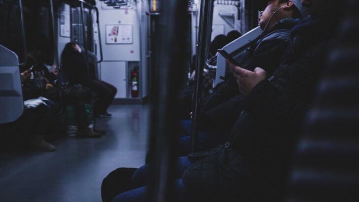 終電、シートに座る疲れた乗客